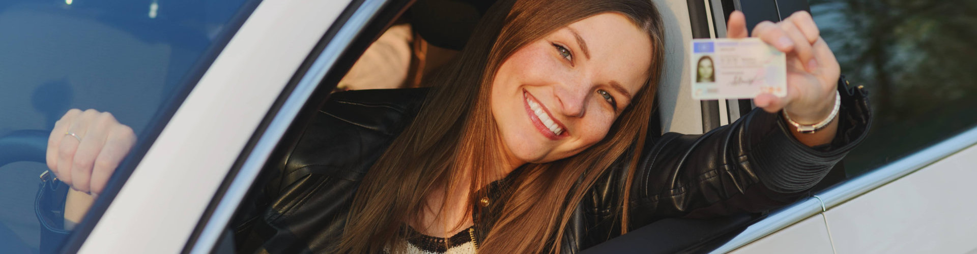 young lady smiling while holding her driver license